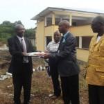 Le recteur, en costume noire et chemise blanche,  remet les clés du bâtiment de la FSTA au SGAD