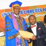 Le recteur remet le diplôme à un lauréat et le félicite.