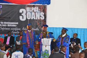 De Gauche à droite, trois professeurs débout, Pr. Dr. Kambale Karafuli, recteur actuel, Prof. Dr. Emérite Léonard Masu-Ga-Rugamika, recteur honoraire et conseiller Spécial du Chef de l'Etat chargé des questions sociales et culturelles et Pr. Dr. Samuel Ngayihembako, recteur honoraire.